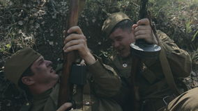 Two soldiers in uniforms and with rifles lie in a stock footage