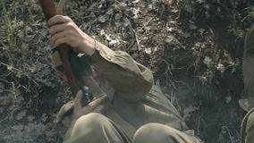 Two soldiers in uniforms and with rifles lie in a. Two soldiers in uniforms and with rifles lying in the trench and dodge bullets in wartime stock footage