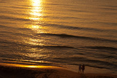 Two solitaire People watching sunrise at sea Stock Photo