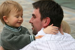 Two sons with father. Two boys are trying to be first Royalty Free Stock Photography