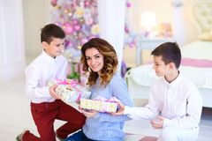 Two sons gifted present for mother near decorated fir tree. royalty free stock images