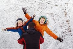 Two sons and his father in winter park.  holding  . Family winte. Two sons and his father in winter forest, outdoor portrait. Father holding two sons. fun, joy Stock Photography