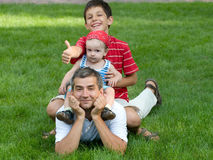 Two sons are sitting on their father's back. Two sons are sitting on their father back holding thumbs up Royalty Free Stock Images