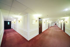 Two spacious light hallways with many wooden doors Stock Image
