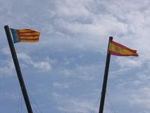 Two flags to the wind of the Spain and of Valencia. Spain. Two spanish flags. Two flags on the wind. Blue sky with white clouds. Clear day. Windy day. Flag of stock images