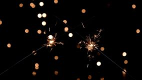 Two sparklers burning in front of ambient lights. Sparkler burning in front of ambient lights. Gun powder sparks shot against bokeh lights background. 4k stock footage