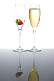 Two sparkling wine glasses with a strawberry. Sparkling wine glasses one  with a strawberry and the other one with wine Royalty Free Stock Images