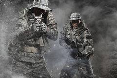 Two Special forces soldiers men holding a machine gun on dark background. Two Special forces soldiers men holding a machine gun go ahead through the fog and the Royalty Free Stock Photos