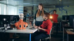 Two specialists are manipulating movements of robot`s face remotely