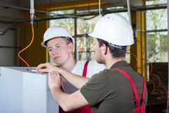 Two specialists repairing factory machine Stock Image
