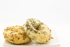 Two specialty bagels placed on white plate Royalty Free Stock Image