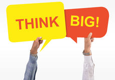 Two speech bubbles in hand with the word think big Royalty Free Stock Photos