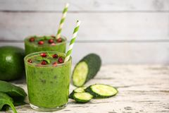 Two Spinach smoothies. Healthy green juice with ingredients on light wooden table. Side view. With Copy space.  stock photo