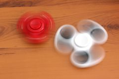Two spinners on wooden background.  stock photo