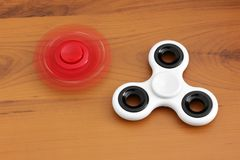 Two spinners on wooden background.  royalty free stock images