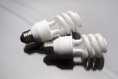 Two spiral bulbs. Two compact fluorescent light bulb on reflective surface Stock Photography