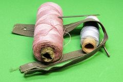 Two spools of thread, needle and zip on a green background royalty free stock images