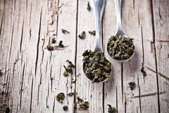 Two spoons of dried green tea leaves Royalty Free Stock Images