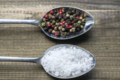 Two spoons with salt crystals and color peppercorns Royalty Free Stock Images