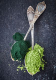 Two spoons of spirulina algae and wheat sprouts powder Royalty Free Stock Photo