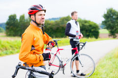 Two sport cyclists having break Stock Image