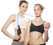 Two sport girls measuring themselves isolated on Stock Photo