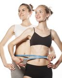 Two sport girls measuring themselves isolated on Royalty Free Stock Photos