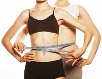 Two sport girls measuring themselves isolated on Royalty Free Stock Photography