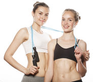 Two sport girls measuring themselves isolated on white Stock Photography