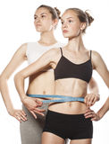 Two sport girls measuring themselves isolated on white Stock Photo
