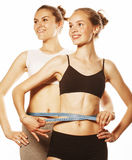 Two sport girls measuring themselves isolated on white Royalty Free Stock Photos