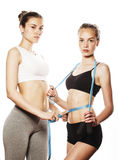 Two sport girls measuring themselves isolated on white Stock Image