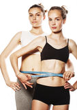 Two sport girls measuring themselves isolated on white Royalty Free Stock Images