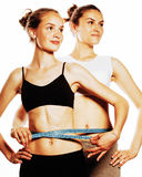 Two sport girls measuring themselves isolated on white Royalty Free Stock Image