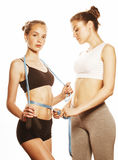 Two sport girls measuring themselves  on white Royalty Free Stock Photo