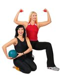 Two sport women with ball and dumbbells Royalty Free Stock Images