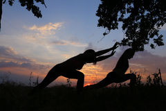 Two sporting girl posing and become into postures of yoga or pil. Graceful girls doing stretching and meditate, relax and bring in tone body, advertising for royalty free stock image