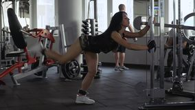 Two guys and a girl in the gym. Two sporting guys and a beautiful young girl in a gym. One guy does a hand exercise using dumbbells. Second guy does the stock video footage