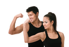 Two sportive people in black showing biceps Stock Photos
