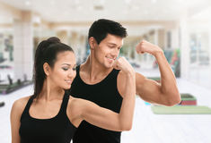 Two sportive trainers in black showing biceps. Two sportive trainers showing their biceps in gym Stock Photography
