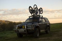 Two sports bicycles over jeep Stock Image