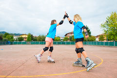 Two sports girl in a tennis Rollerblade give you clap their hand Royalty Free Stock Photos
