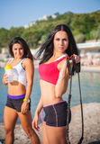 Two sports girls on a beach Stock Photos