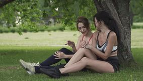 Two sports girls rest after training in the park. Young women sitting on the grass under a tree stock video