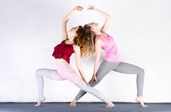 Two sports girls train yoga in a fitness class.Young women stretching stock images
