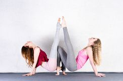 Two sports girls train yoga in a fitness class. Pair of young women stretching royalty free stock image