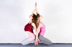 Two sports girls train yoga in a fitness class. Groups of young women stock photo