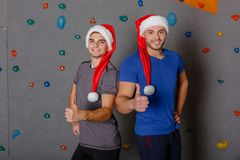 Two sports guy in santa hats smile and show thumb up. Against the wall for rock climbing. Stock Image