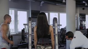 Two guys and a girl in the gym. Two sports guys hangs weight plates on the bar. Beautiful girl with dark hair and a short sports t-shirt. Girl stands with her stock video footage
