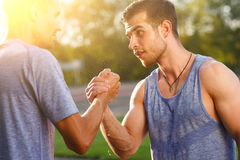 Two sports men met during a workout and shake hands. Image with lens flare effect Royalty Free Stock Photos